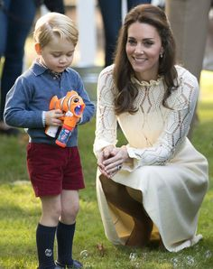 Prince George uses a bubble maker next to a crouching Duchess of Cambridge