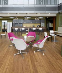 This breakout area has pink and white swivel chairs at wood tables, beige sofa seating around the perimeter wall and wood floors for a natural finish.The kitchen area at the far end of the room includes wood breakfast bar, white bar stools with black legs and pendnat lighting.  The space is visible from the other areas of the office, taking a central location in this workplace.  See more of this workplace fit out by clicking the image.