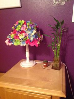 Lampshade makeover with some brightly colored silk flowers! This lampshade was one huge sticker so no messy glue guns were needed! I love how it pops against the dark purple wall!