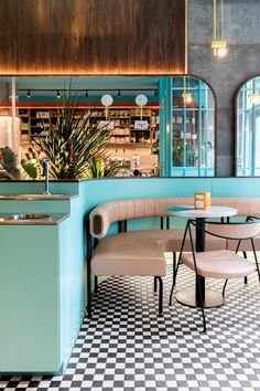 All of Caffettiera Caffé Bar's available space offers a chance for customer interaction. The banquettes intersect at a self-service station, behind which a backlit planter is enhanced by the mirrors' reflection.