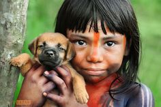 Indian Girl with Puppy - A girl covered in traditional body paint holds her puppy, on the day of a festival which I was privileged to attend. Taken in the Amazon rainforest in a community near to the town of Maraba. Photo by David Lazar.