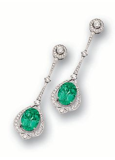 PAIR OF EMERALD AND DIAMOND PENDENT EARRINGS.  Each stylised drop adorned with brilliant-cut diamonds and millegrain decoration, housing an oval emerald weighing 3.83 and 4.03 carats respectively, suspended from similarly decorated tapered bars and brilliant-cut diamonds, mounted in 18 karat white gold.