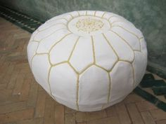 White pouf with gold stitching