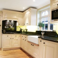 L-shaped kitchen with white cabinetry, black granite worktops and butler sink