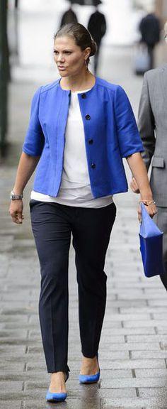 La princesse Victoria affiche un look dominé par le bleu électrique de sa veste courte, sa pochette et ses escarpins. Cette tonalité illumine sa tenue constituée par ailleurs d'un top blanc et d'un pantalon bleu marine.