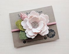 This listing is for one wool felt big flower headband in blush pink and soft coral. The flower is accented with a rose gold metallic faux leather center and a mix of light and dark green leaves. The flower and leaves measure approximately 3.75 x 3. Measurements of the flower and