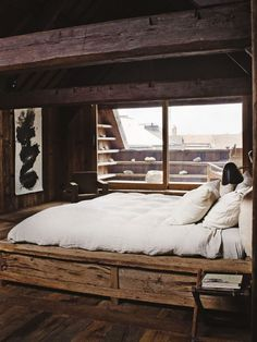 Exposed oversized beams, wood flooring, recycled wood bed frame