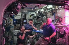 NASA astronauts Scott Kelly (right) and Kjell Lindgren (center) with Kimiya Yui of JAXA snack on freshly harvested space-grown red romaine lettuce as part of the Veggie experiment.