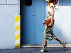 A striped midi dress is worn over a white tee, with a brown clutch and snakeskin booties