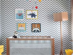 Toda a decoração deste quarto teve início a partir da escolha do papel de parede em zique-zague. Os quadros cheios de cor colocados na parede fazem o ambiente divertido, assim como o móbile acima do berço. Projeto do escritório Trix Interiores