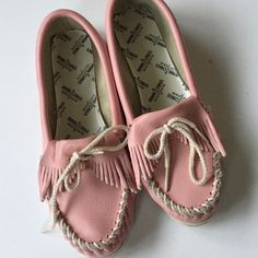 Minnetonka leather moccasins Cute pink moccasins with fringe and tie front. These have been worn but are in good shape. Smoke-free/pet-free home. Minnetonka Shoes