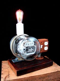 This creation features a reclaimed, working vintage electric meter. Charge your device, turn on the lamp...watch the meter record the usage. The meter is true vintage and is mounted to a handmade reclaimed wood base which has been lightly stained to bring out some of the detail. On top of the meter is a reclaimed commercial grade large porcelain socket in which a NEW medium base socket has been securely mounted. The use of the large socket provided needed visual balance on the meter. This…