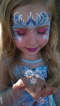 Elsa frozen Face paint by Melinda Thompson   www.facebook.com/tucsonfacepainter.  One stroke painting. Girl face paint. One-stroke frozen crown. Snow flake facepaint. Elsa glitter mask.