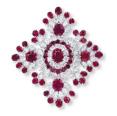 The openwork lozenge shape panel of foliate design, centering upon an oval-shaped ruby, within a brilliant-cut diamond and circular-cut ruby two-tiered surround and marquise-cut diamond trim, extending to the oval-shaped ruby and marquise-cut diamond quatrefoil clusters, alternating with old European-cut diamond and circular-cut ruby accents, mounted in 18k white gold, 5.8 cm long, with French assay mark for gold  Signed Van Cleef & Arpels