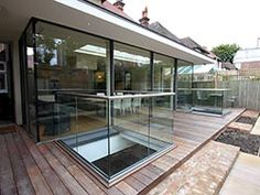 Sliding glass doors (shown closed) to the rear extension and glass balustrades allowing light into basement courtyard below