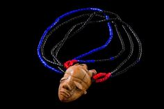 """Anthropomorphic miniature mask """"ikoko"""" - D. R. Congo, Pende - ivory, attached to a necklace of black, blue and red glass beads, threaded on plant fibre strings"""