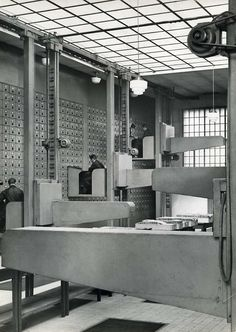 Photographer:   J. Ehm    Title:Archives.     Archives of French insurance company. The workstations move up, down and sideways, along the archive boxes. France, 1937.