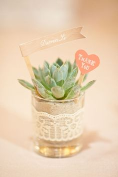 Potted succulent with flag as place card in a shot glass with the bride and grooms wedding date on it. Perfect favor and place marker combination.
