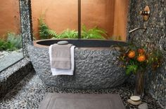 A unique twist on the outdoor shower. Glass walls, a granite tub and river-rock floors and walls make this one amazing bathing room.
