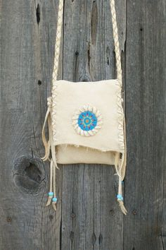 This beaded leather purse is simple, light, and is made of elkskin leather. It features a 48 braided strap. This handbag can also be tied around your