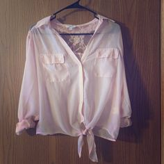 Light Pink Laced Back Button Up Shirt Light pink button up shirt with laced upper back. 100% Polyester, in very good condition. Sleeves can be rolled up, two pockets in front. Will most likely need to wear something underneath because very thin material. Tops Blouses
