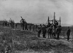 Belgian troops man row of antiaircraft guns mounted on pivots