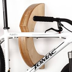 A stylish handmade bicycle rack designed to turn your bike into a work of artOriginally designed to help a GB triathlete store the bikes in her flat. Perfect for elevating your pride and joy to the status it deserves, hanging from the wall like a work of art. Conceived and made in England, the design transfers the weight of the rack and bike back down into the wall making it very stable and easy to install.Constructed from top grade birch plywood, complete with a durable oil finish…