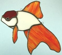 This Redcap Goldfish (Oranda) suncatcher measures approximately 9.5 inches by 7 inches . Swirled red and white stained glass was used for this fish. All our Stained Glass art is hand made in our art studio here in the coastal bend of Texas.  We are proud members of the following ETSY teams:  CASTTEAM (Christian Artists Street Team)  CGGE (Creative Glass Guild of Etsy)  teametsytx(Etsy Texas Crafters)  Designstyleguide  We appreciate your support of American artists.