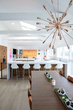 Optando pelo branco nas paredes, o casal utilizou cores vibrantes nos detalhes, como a persiana e a mesinha laranja. O neon, uma das várias referências ao pop art espalhadas pela casa, deu personalidade ao espaço.