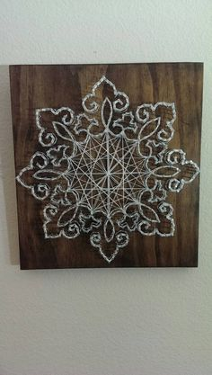 This is a wood/nail/string art piece that I made by hand. The panel is approximately 11x12x1 (height including the nail). The wood is stained with