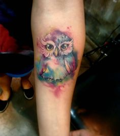 Wasserfarben Tattoo von einer kleinen Eule mit großen Augen in vielen Farben