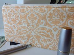 This 100% cotton fabric is a soft shade of peach on a white background, in a classic damask design. Padded, and fully lined with baby's breath fabric.  The shape of the case is sleek with curved corners at the top towards the zipper for a secure side-to-side closing. The bottom edges are straight to the bottom. This case is flat overall.