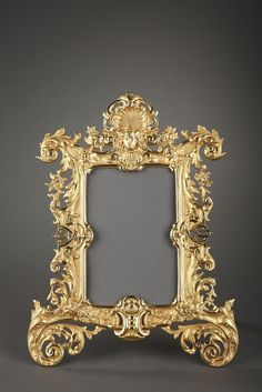Gilt bronze frame richly sculpted with garlands of flowers, roses and scrolling foliate terminating with scrolling foliage. Openwork interlacings on both sides and a mascaron crowned with a