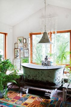 Vintage bath in a Norwegian cabin - colorful floor tiles (turtles!), an enormous beaten bathtub, bird etchings on the walls, shell panel curtain,  house plants  #bohemian #interior