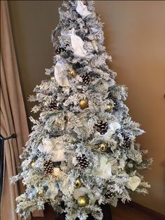 Flocked White Christmas Tree with gold ornaments and white pinecones
