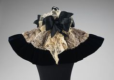 This youthful cape evokes the highly feminine fashions of the time.  Although it is far more decorative than protective, its bows, fur trim and lace would flatter the wearer's face and enhance the beauty of her overall ensemble