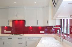 {Natural & manmade materials}: Opticolour oriental red glass splashbacks, also showing socket cutouts