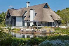 Prachtige moderne witte villa met rieten dak, veel raampartijen en gestucte gevels