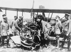 German officers examining the wreckage of a British biplane.