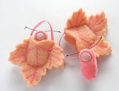 A hand embroidered peach leaf ornament with a pocket for a little removable 1-1/2 caterpillar doll. The leaf is 3 and 3 tall, it is made from