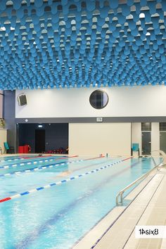 The wave-like curves of our acoustic baffle named Bubble looks natural in a gym environment reducing the notorious echo of a public swimming pool. #baffles #acousticbaffles #interiors #interiordesign #architecture #officedesign #officedecor #workplaceinteriors #14six8 #officeinspiration #officeinteriors #interioracoustics #acoustics #acousticsystem #suspendedacoustics #baffle #contemporarydesign #contemporaryinteriors #designinnovation #interiorproject #slats Acoustic Baffles, Office Interiors, Contemporary Interior, Wall Tiles, Office Decor, Sustainability, Swimming Pools, Innovation, Curves