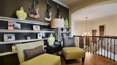 #Decorate your #upstairs #living #area with floating #shelves and unique #art to spice up the #seating #area. #guitars #woodfloor #staircase