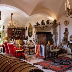 A large carved stone fireplace with an ornate cast-iron chimney plate is the focal point of this living room in Switzerland