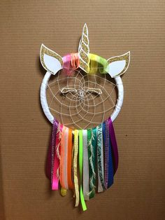 "Handmade one of a kind unicorn dream catcher. The perfect gift for any little girls room. A unique gift that is sure to stand out. This dream catcher has a white ribbon hoop that is about 9"" wide and hangs about 19"" long. This unicorn dream catcher features a gold glitter horn and face. And"