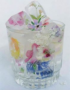 Freeze 1 layer of water in an ice cube tray, place your flower on top, add water and freeze again!  such a sweet party idea