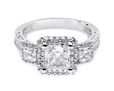 HT2526 PR 6 With glamour to spare, this three stone princess ring is a bold and beautiful blast of diamonds. A pretty profile with diamond crescents and double halos surrounding each stone make this ring distinctive and elegant