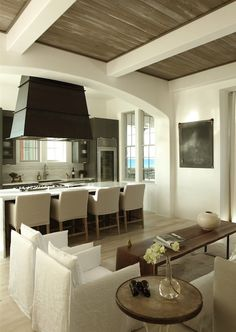 Open concept kitchen with black range hood over gas cooktop on waterfall kitchen island lined with slipcovered bar stools.
