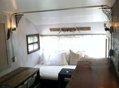Vintage camper interior remodel / 1955 Trotwood / refurbished pallet accents / live edge wood slab bar counter / rustic industrial