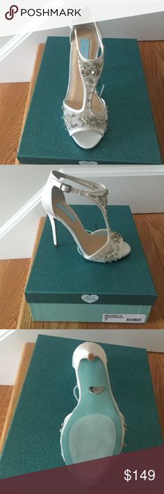 Blue by Betsy Johnson Holly Stunning!! New in box- never worn! Ivory sarin with bead and pearl detail. Peep toe sandals with T strap and side buckle. The heel height is 4.5 inches. I believe they are SOLD OUT right now! These are the Perfect wedding shoe! I bought them for my own wedding, and decided on something with less heel as I got married outdoors. Feel free to ask any questions! Thanks!! Betsey Johnson Shoes