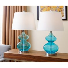 These Abbyson Living Sophia table lamps will be a stylish addition to your home. The transparent French blue glass base is striking below the ivory lamp shade. These lamps will bring balanced harmony to your room.